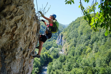 Woman on via ferrata at Suncuius, Bihor county, Romania, on a bright sunny day, with Crisul Repede defile below her.