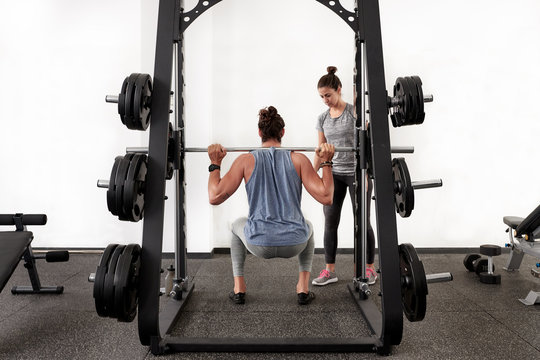Man doing squats in machine with woman standing near