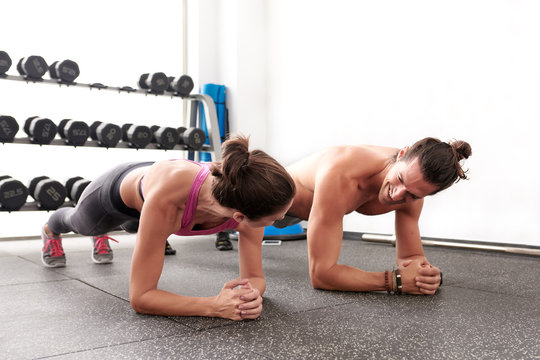 Cheerful sportive people doing abdomen exercise together