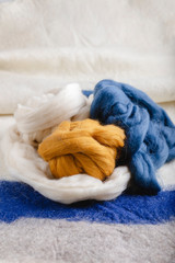 Skeins of wool resting on a woolen fabric