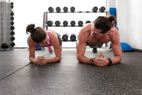 Sportive man and woman doing plank exercise