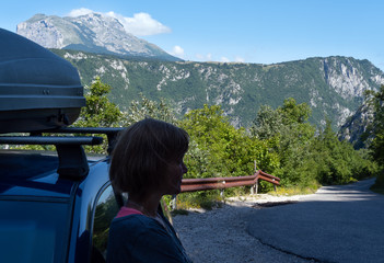 Woman near car (unrecognizable) on secondary countryside road through mountain Durmitor National Park, Montenegro.
