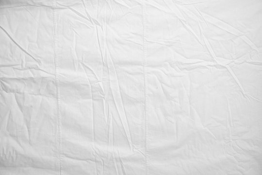 White Crumpled Bed Sheet Background Texture. white fabric top view. pleats on light fabric