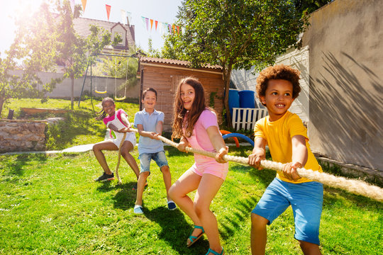 Group of kids play pulling rope game on the lawn