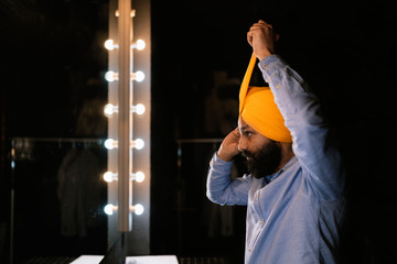 Indian sikh man standing by the mirror and putting turban