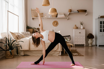 Fit pregnant woman on yoga mat at home
