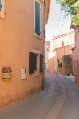 A narrow street in the beautiful French village of Roussillon, where the buildings are made with colorful.