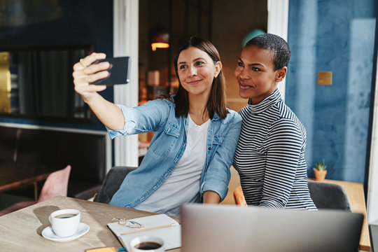 Smiling female entrepreneurs sitting together in a cafe taking s