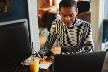 Female entrepreneur writing notes and working online in a cafe