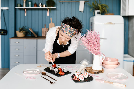 Young woman decorating desserts