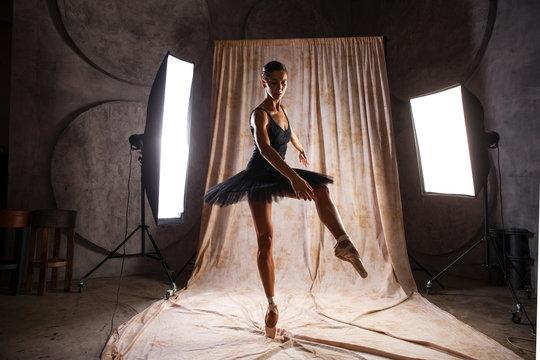 Full body portrait. Russian ballerina in a black dancing suit is posing in dark studio