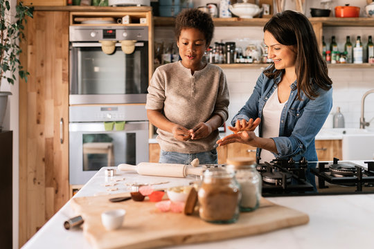 Black child and woman at table with rolling pin and different ingredients