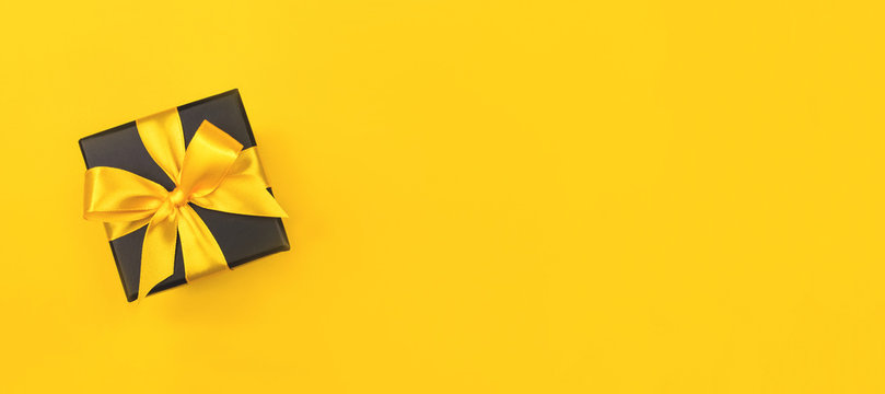 Black gift box with bow on yellow background.