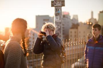 young man taking photos of friend on Brooklyn bridge