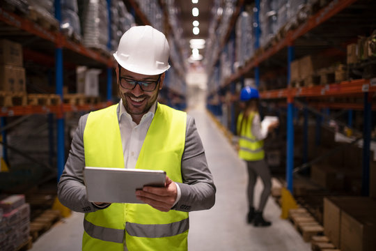 Warehouse supervisor reading report on tablet about successful delivery and distribution in warehouse logistics center. In background coworker checking inventory and productivity in storage area.