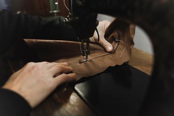 Man stitching textile in atelier