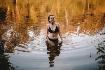 Seductive woman in a bikini walking in lake