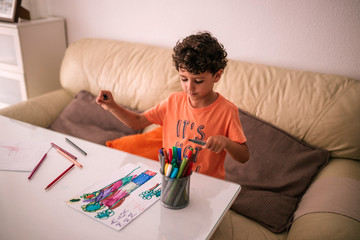Curly-haired child is at a table painting drawings with colors