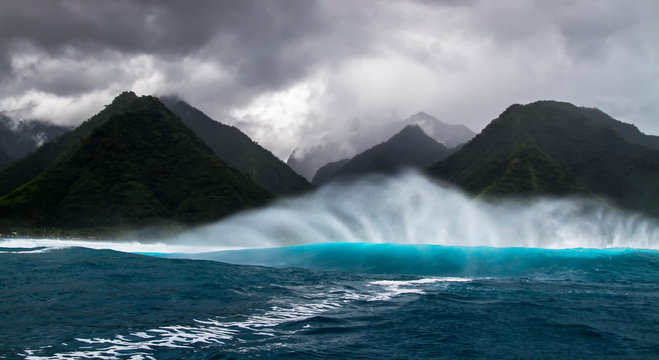 Wave breaking with mountains in the back in Tahiti
