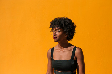 Portrait of young woman with afro hair on a yellow background