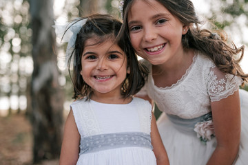 Little girl in communion dress smiling with her little sister in forest