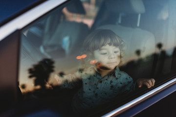 Toddler boy in driver's seat of van looking at the sunset