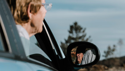 A old woman out of focus with her head out the window and focus on the elderly man reflected in the car mirror