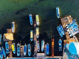 Foto op Plexiglas Stad aan het water From above motorboats and wooden piers located on calm sea in harbor