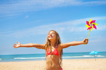 Girl with pinwheel on the beach happy and smiling