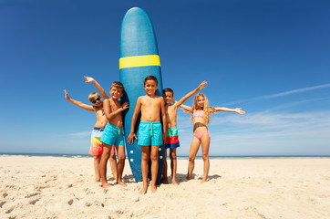 Many kids stand with surfboard on the sea beach