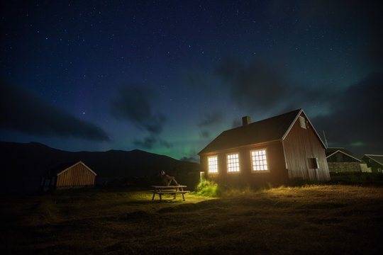 Person outside cabin t night looking at night sky with aurora borealis