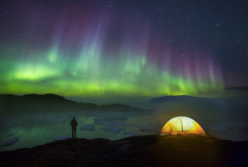 Person by tent overlooking ice fjord and icebergs under starry night sky and aurora borealis