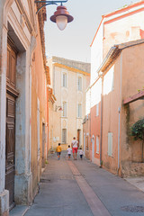 A narrow street in the beautiful French village of Roussillon, where the buildings are made with colorful. Luberon, France.