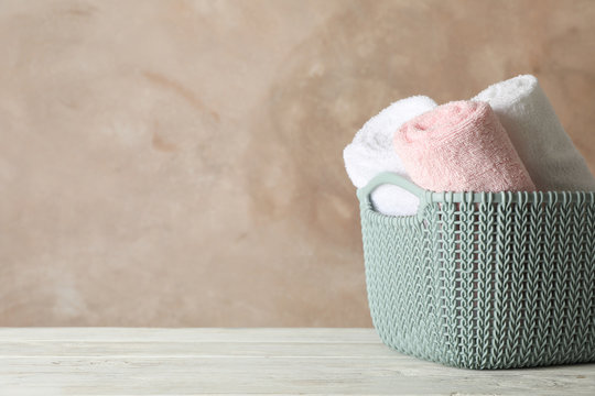Basket with clean laundry on wooden board, space for text