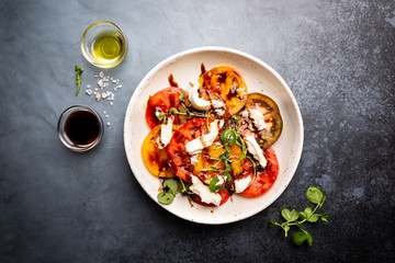 Fresh colorful tomatoes salad with mozzarella and balsamic vinegar on a plate, top view