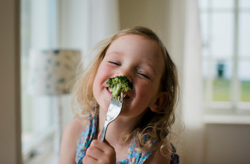 Young girl laughing with a messy face whilst eating broccoli