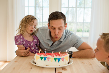 Dad sat with his daughter and son blowing candles on a birthday cake