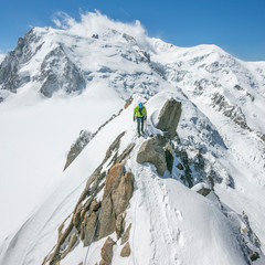 A male alpinist heads across an exposed knife-edge ridge on Mont Blanc