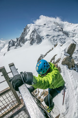 Over the railing! Alpinist topping out on the Cosmiques Ladder