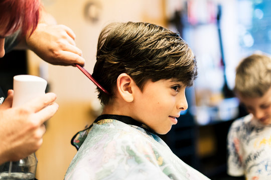 Happy boy with new look after cutting hair in salon