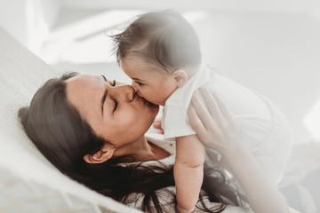 Mother kissing baby daughter hammock in natural light studio