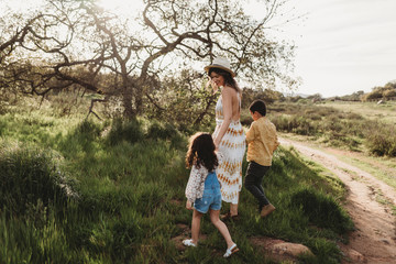 Side view of mother and children walking into field together