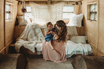 Mother and daughter cuddling and laughing in boho studio setup