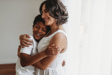 Mother hugs school-aged son in smiling embrace