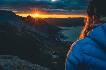 Photographer watching sunrise from mountain ridge
