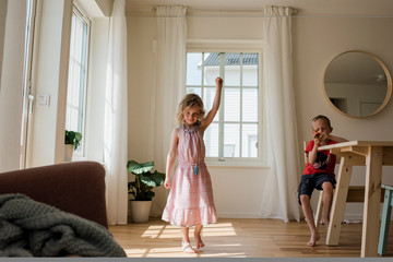 Young girl dancing and playing at home with her brother