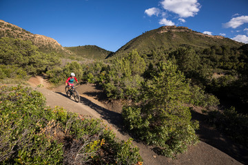 Mountain biker riding a trail in the mountains.