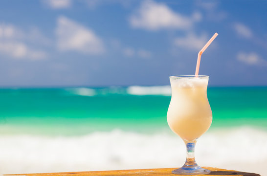 picture of pina colada and sunglasses on tropical beach