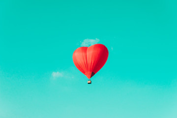 Acrylic Prints Balloon Red hot air balloon in the shape of a heart against the blue sky and some light clouds.