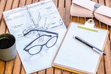 Bureau d'architecte ou ingénieur du bâtiment - bureau féminin en bois avec un plan de construction et fournitures  de bureau lunettes tasse à café stylo trousse